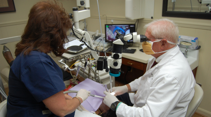Dentist at microscope conducting research with assistant to his left